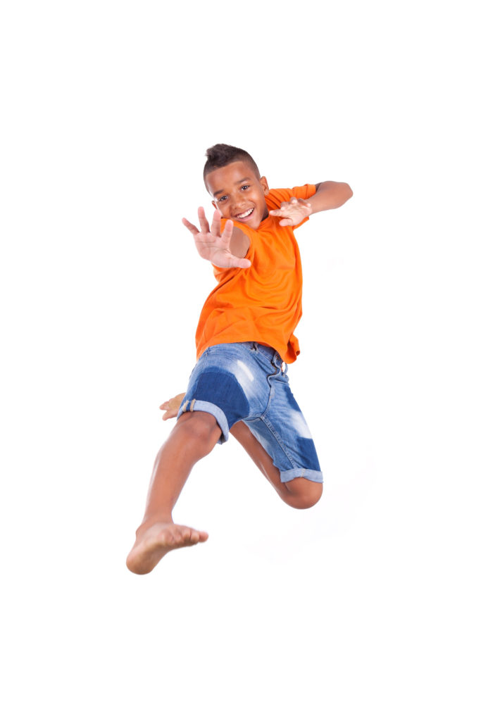 21307796 - portrait of a cute teenage black boy jumping over white background - african people